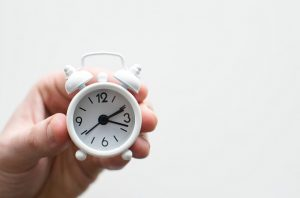 Hand Holding A Small White Clock- Benefits Of Hiring A Junk Removal Company Pensacola- Something Old Salvage 6505 North W St Pensacola Fl 32505 (850) 758- 9900 https://www.somethingoldsalvage.com