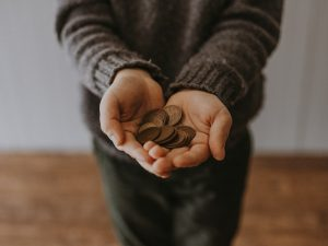 Hand Holding Coins- Benefits Of Hiring A Junk Removal Company Pensacola- Something Old Salvage 6505 North W St Pensacola Fl 32505 (850) 758- 9900 https://www.somethingoldsalvage.com